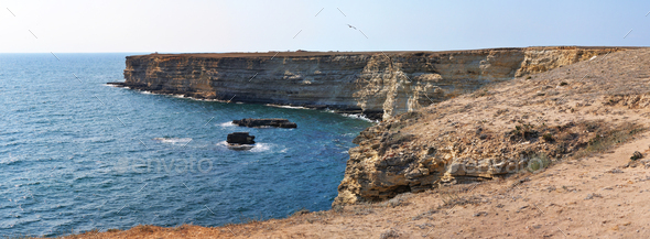 Panoramic landscape of Black sea rocks at coastline with clear blue waters in Crimea - Stock Photo - Images