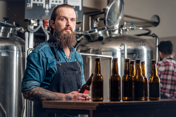 Two men presenting craft beer in the microbrewery. - Stock Photo - Images