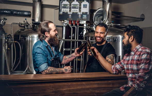 Stylish three men drinking craft beer in the microbrewery. - Stock Photo - Images