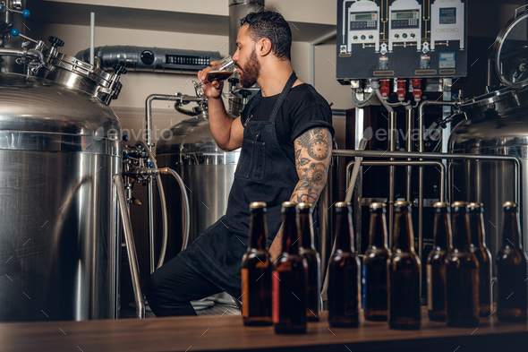 Black male manufacturer tasting beer in the microbrewery. - Stock Photo - Images
