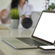 Laptop blank screen and smartphone on wireless charger with background people are working blurred. - PhotoDune Item for Sale