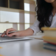 Girl holding a pen in hand on a laptop keyboard. She is working in a modern office. - PhotoDune Item for Sale
