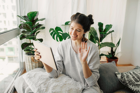 Happy hipster girl chatting on tablet, communicating live with family  from home - Stock Photo - Images