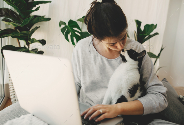 Young woman giving kiss to her cat and working on laptop - Stock Photo - Images