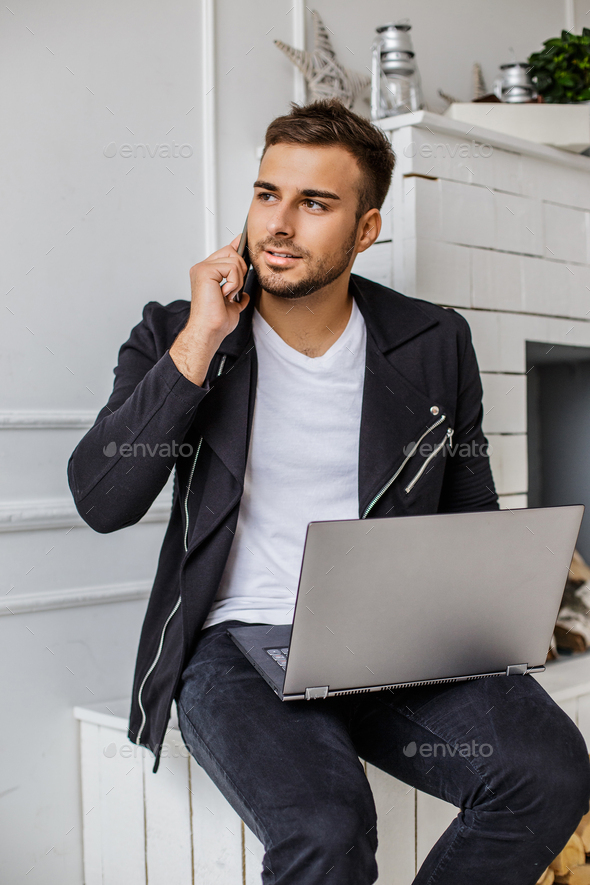 A man using laptop near fireplace. - Stock Photo - Images