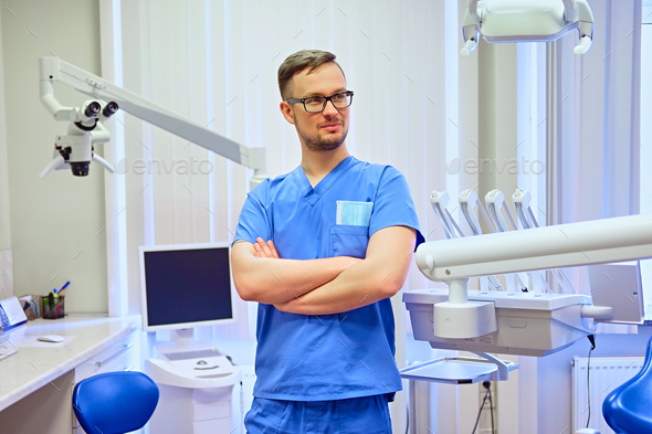 Male dentist in a room with medical equipment on background. - Stock Photo - Images