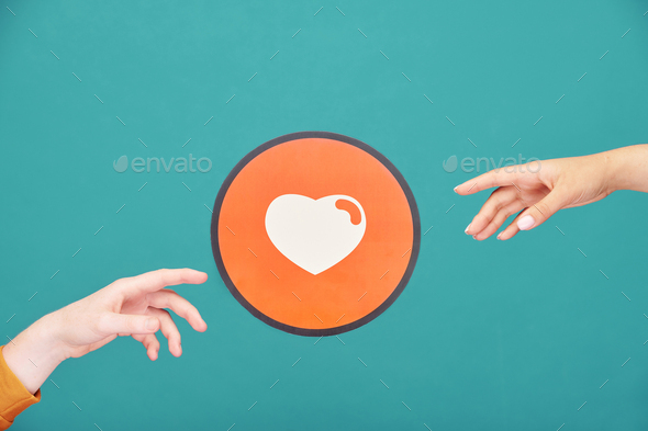 Hands of young man and woman reaching out for picture of heart in red circle - Stock Photo - Images