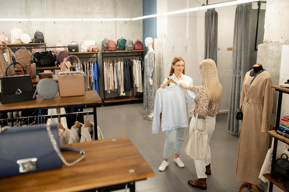 Young female shop assistant showing white sweatshirt to blond elegant buyer - Stock Photo - Images