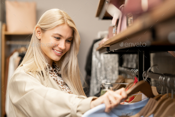 Smiling young blond woman with long hair looking through new fashion collection - Stock Photo - Images