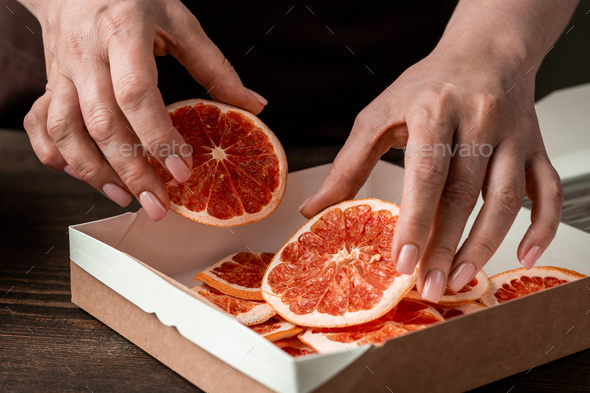 Hands of woman putting homemade dried orange or grapefruit slices into box - Stock Photo - Images