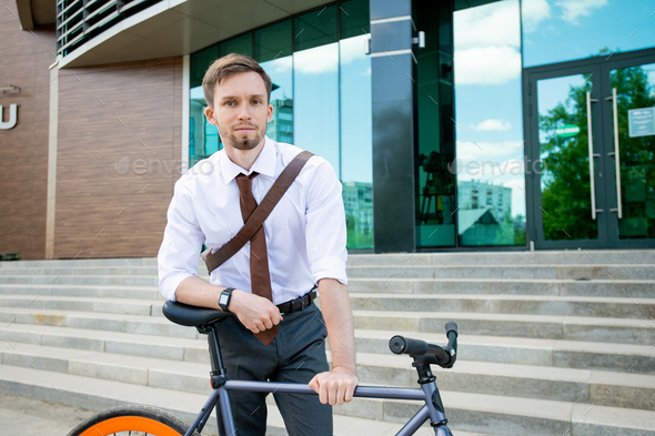 Happy young successful businessman looking at you while leaning on his bicycle - Stock Photo - Images