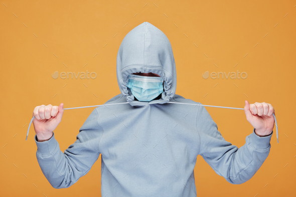Contemporary young man in hoodie and protective mask stretching cords - Stock Photo - Images