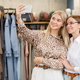 Two cheerful females in elegant casualwear making selfie in boutique environment - PhotoDune Item for Sale