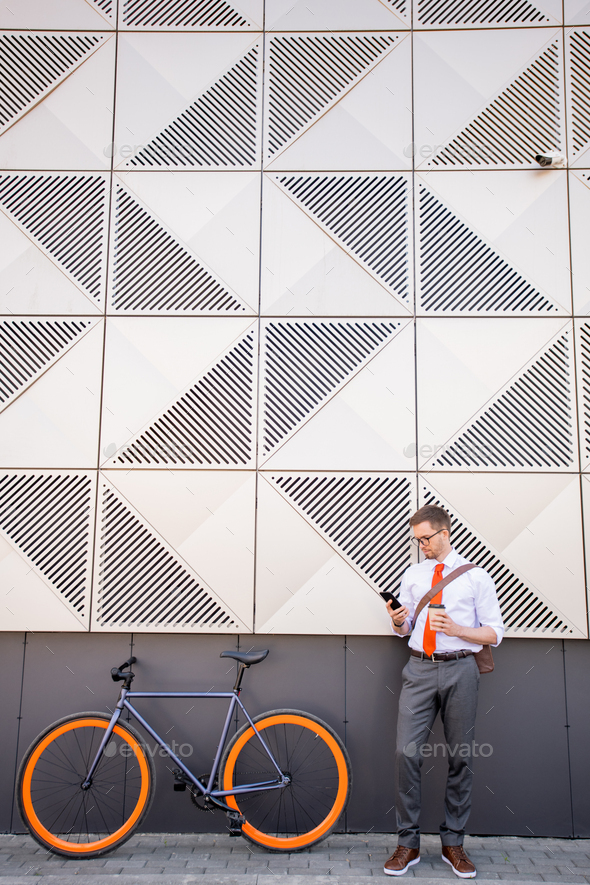 Young man in smart casualwear standing by wall of large modern business center - Stock Photo - Images