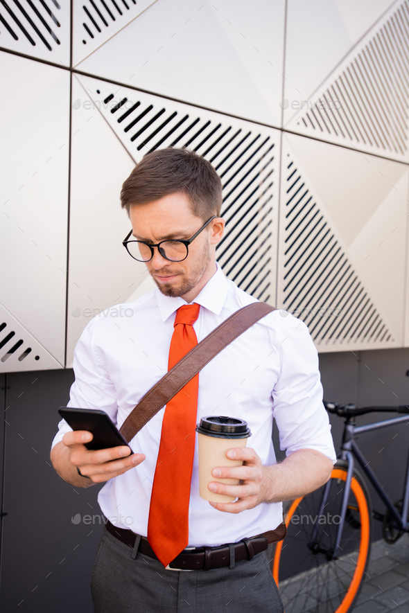 Young serious businessman scrolling in smartphone and having coffee - Stock Photo - Images
