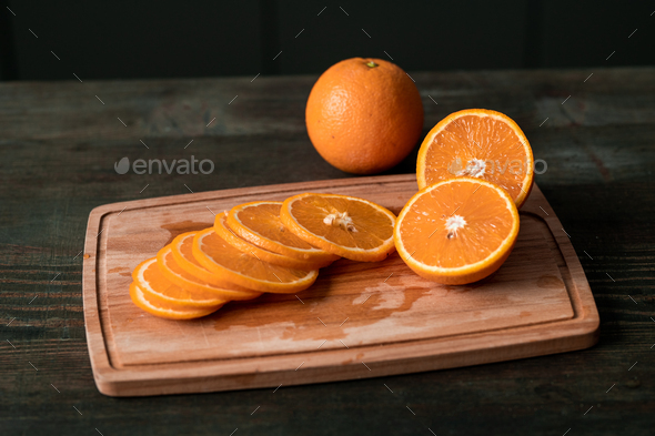 Group of fresh orange slices and halves of the fruits on wooden chopping board - Stock Photo - Images