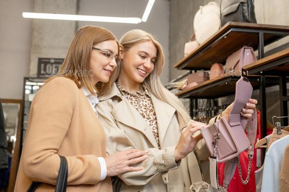 Two cheerful women in smart casualwear choosing handbags for new season - Stock Photo - Images