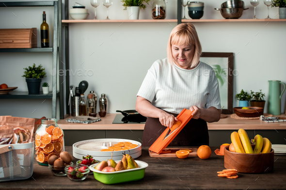 Blond pretty housewife standing by kitchen table and cutting fresh oranges - Stock Photo - Images