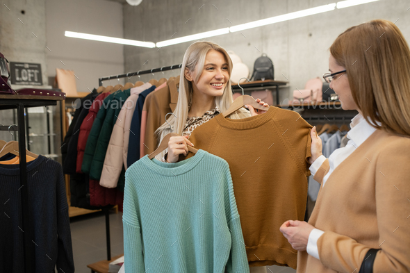 Young smiling female looking at her mother while standing among racks - Stock Photo - Images