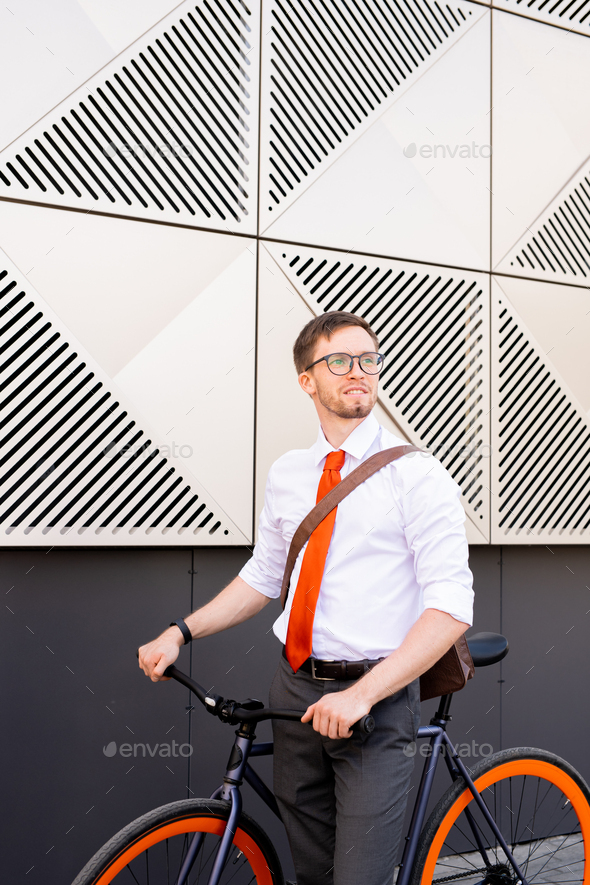 Young successful office manager in shirt, tie and trousers looking aside - Stock Photo - Images
