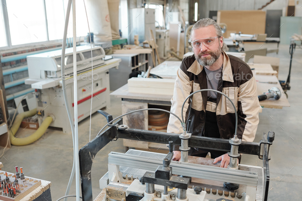 Senior worker of factory bending over industrial machine for processing wood - Stock Photo - Images
