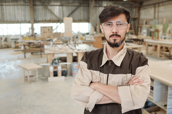 Young serious worker or engineer of furniture producing factory in uniform - Stock Photo - Images