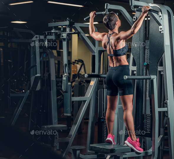 Female with short hair doing pull ups in a gym. - Stock Photo - Images