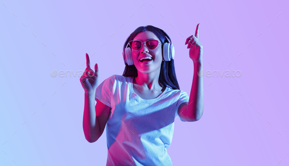 Dancing in headphones. Asian girl with glasses enjoys favorite song - Stock Photo - Images