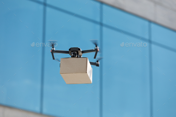 Innovation drone fast delivery concept, drone with cardboard parcel - Stock Photo - Images