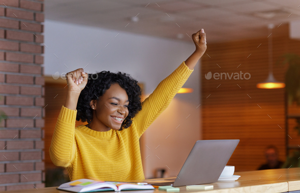 Emotional woman looking at laptop and screaming, working at cafe - Stock Photo - Images