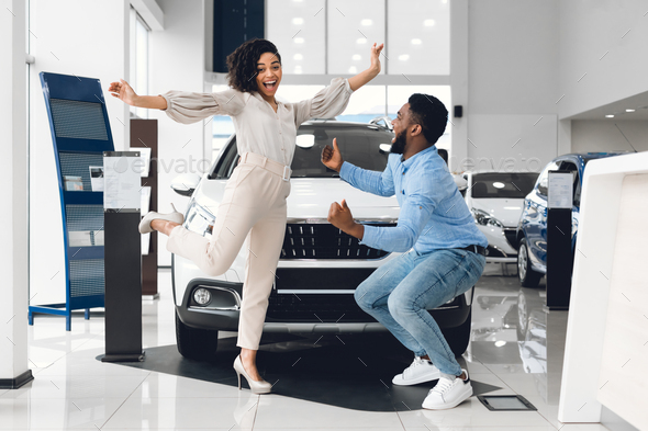 Joyful African Couple Jumping Buying Automobile In Dealership Showroom - Stock Photo - Images