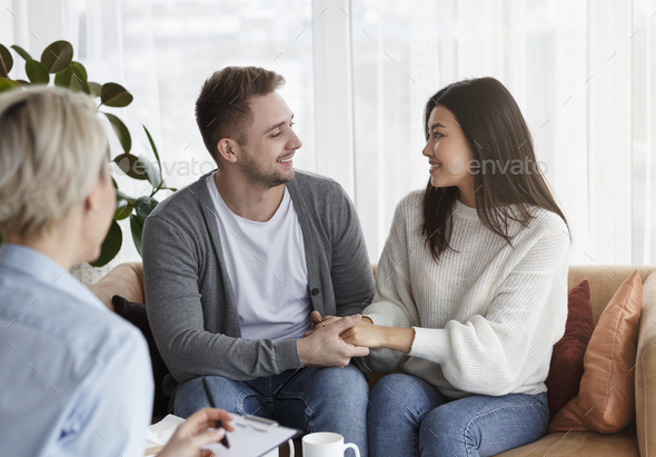 Happy Couple Holding Hands Reconciling After Therapy Sitting In Office - Stock Photo - Images