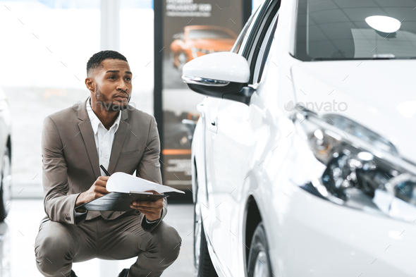African Man Sitting Near New Vehicle Checking Auto In Store - Stock Photo - Images