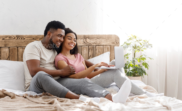 Black couple in love using laptop in bedroom at home - Stock Photo - Images