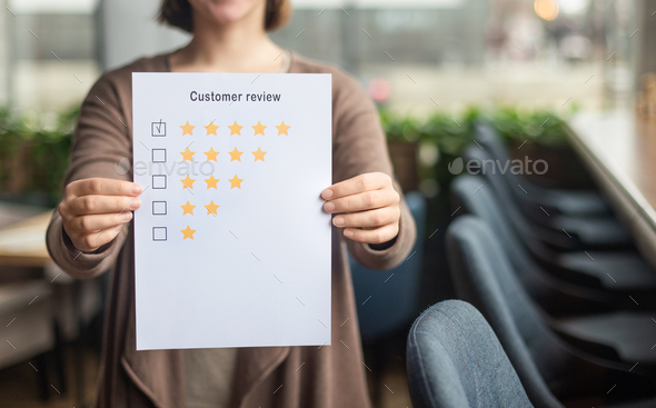 Blurred female holding paper sheet with five star rating - Stock Photo - Images