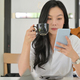 Asian woman is checking messages on a smartphone and drinking coffee in a comfortable office. - PhotoDune Item for Sale