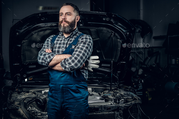 A man near the car in a garage. - Stock Photo - Images