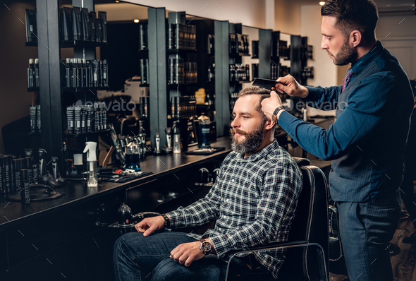 Stylish male hairdresser doing haircut to a bearded male in a sa - Stock Photo - Images