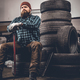 A man sits on an old tire in a garage. - PhotoDune Item for Sale