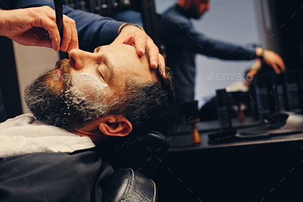 Barber shaving bearded male with a sharp razor. - Stock Photo - Images