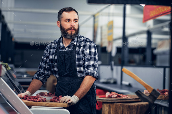Bearded butcher serving fresh cut meat. - Stock Photo - Images