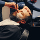 Barber shaving bearded male with a sharp razor. - PhotoDune Item for Sale