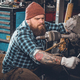 Bearded male repairing car's engine in a garage. - PhotoDune Item for Sale