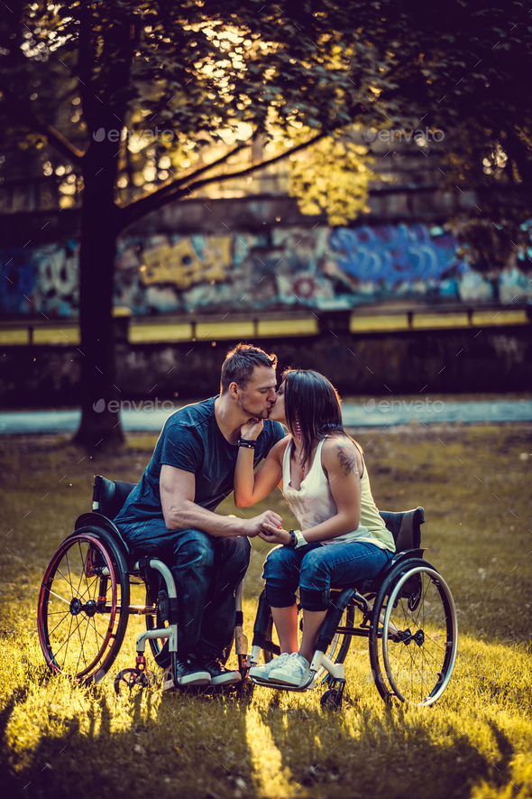Handicapped young couple on two wheelchairs kissing . - Stock Photo - Images