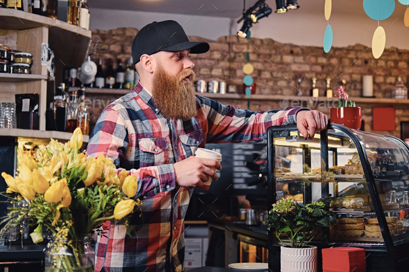 A man dressed in a fleece shirt posing at the counter in a coffe - Stock Photo - Images