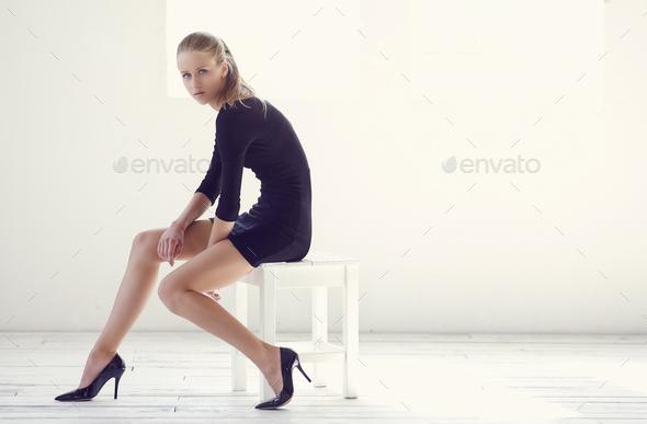 Slim female in black dress sitting in white room. - Stock Photo - Images