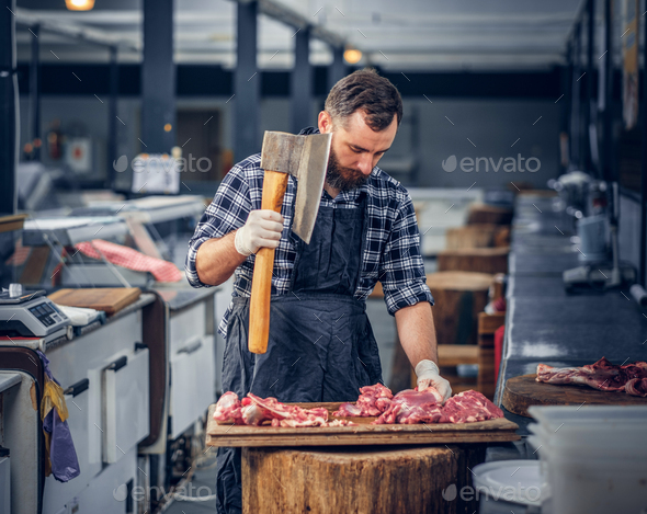 Bearded butcher cuts meat with axe. - Stock Photo - Images