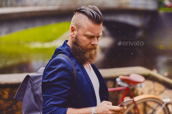 Bearded hipster male using smartphone in a park near river. - Stock Photo - Images