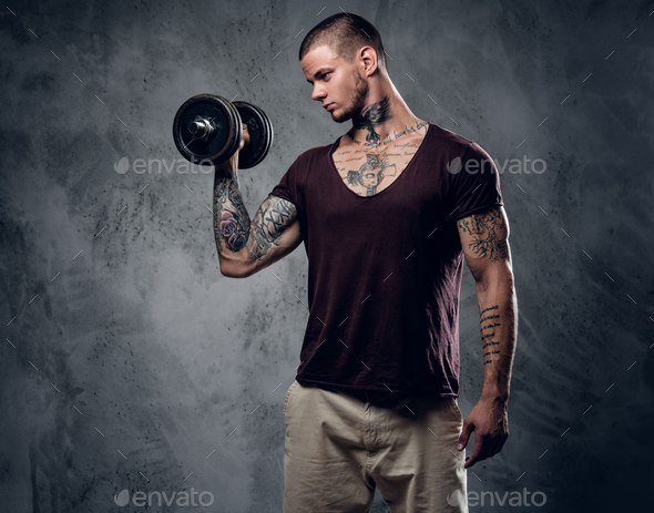 A man holds dumbbell over grey background. - Stock Photo - Images