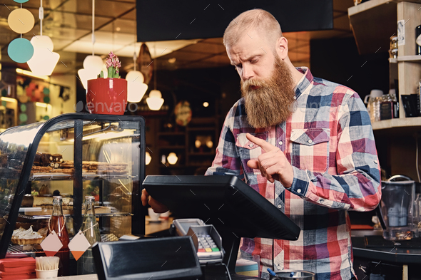 A man at the counter using cash register in a coffee shop. - Stock Photo - Images